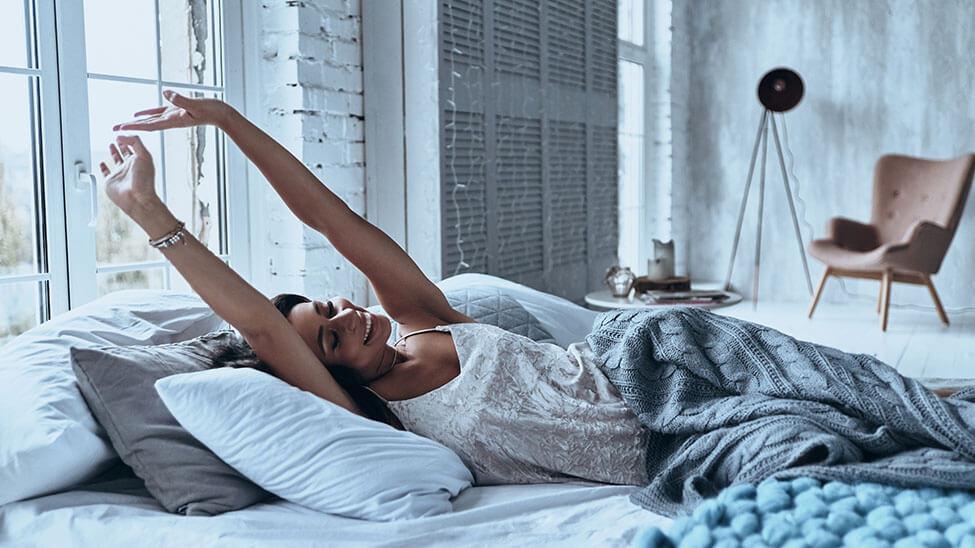 Junge Frau streckt sich morgens entspannt im Bett vor dem Aufstehen