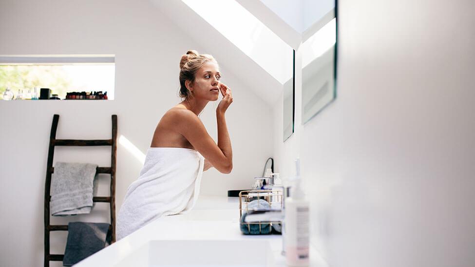 Frau cremt sich im Bad ein, um sich gegen Pickel zu schützen