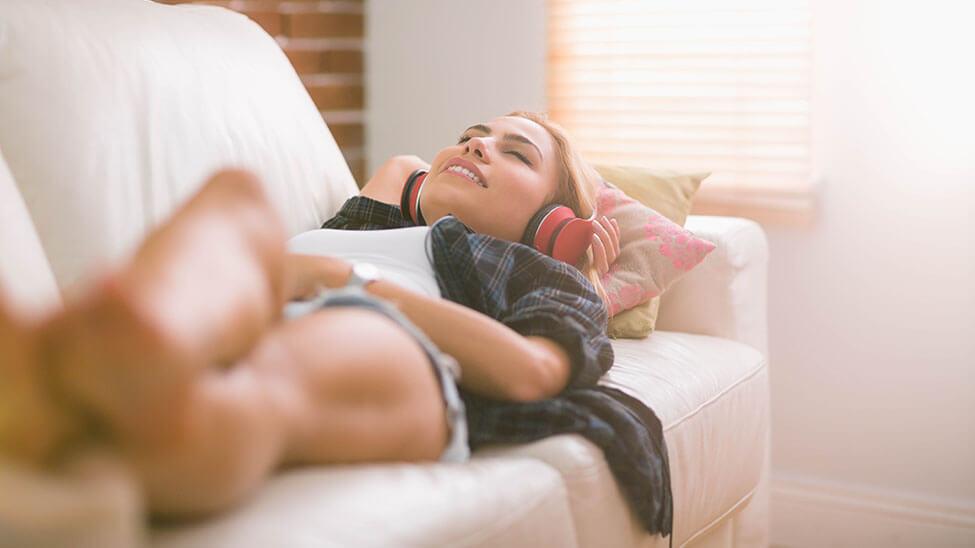 Junge Frau liegt entspannt auf Sofa und hört Wellnes Musik über Kopfhörer