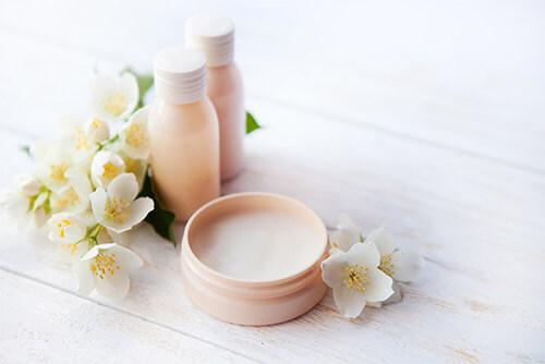 Offenes Wellness-Creme-Produkt & Duft-Gläschen mit Blumen verziert