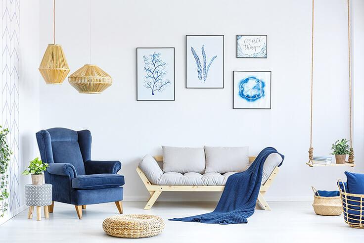 Helles, aufgeräumtes Wohnzimmer in blau, mit Sessel, Sofa, Decke, Schaukel und Bildern an der Wand