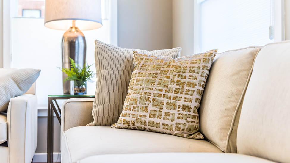 Cremefarbene Wohnzimmer-Couch mit verschiedenen Kissen und einer Lampe im Hintergrund