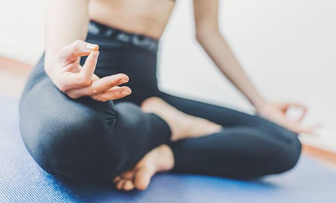 Frau meditiert in Schneidersitz auf Yogamatte