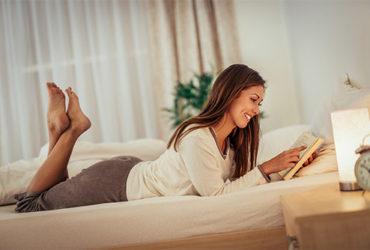 Junge Frau liest ein Buch auf dem Sofa als Bestandteil eines Abendrituals