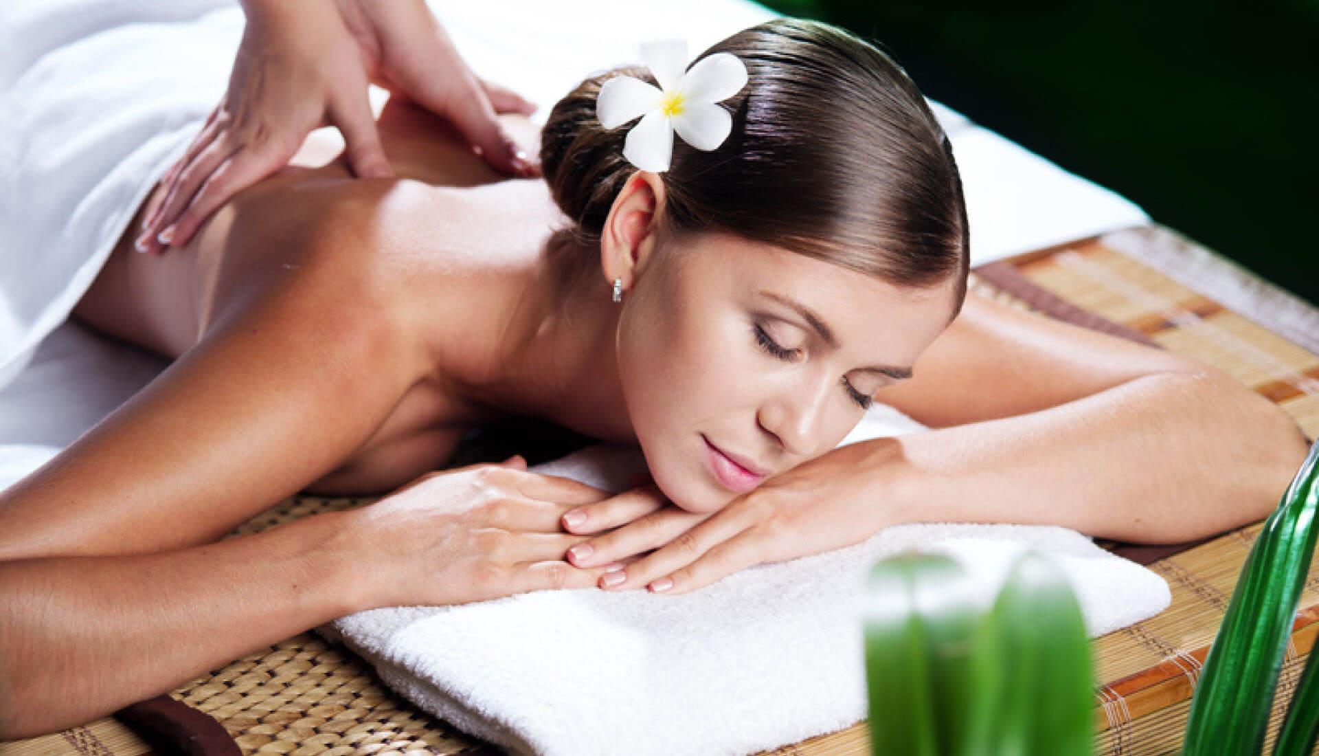 Aromaölmassage für eine schöne Frau, die auf einer Bambusliege und einem weißen Handtuch liegt