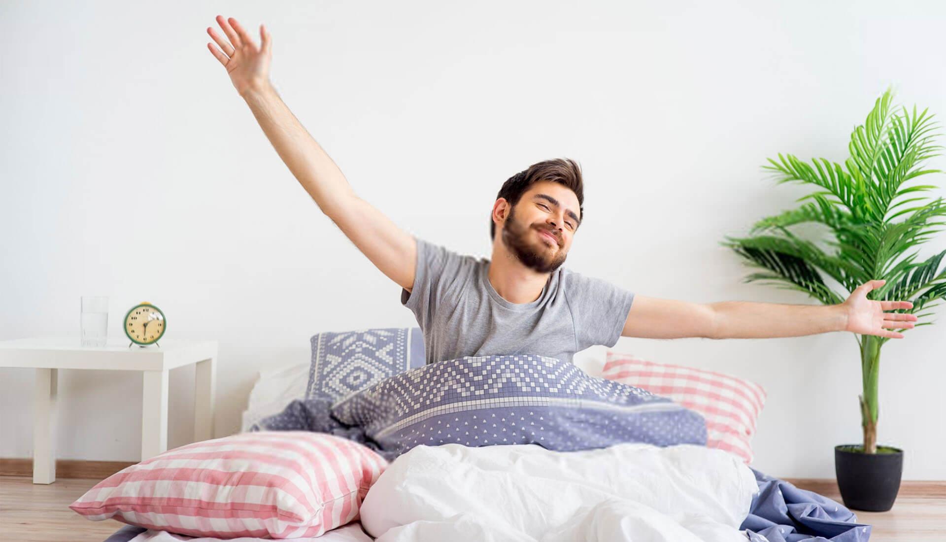 Junger Mann streckt sich fröhlich beim Aufstehen am Morgen im Bett
