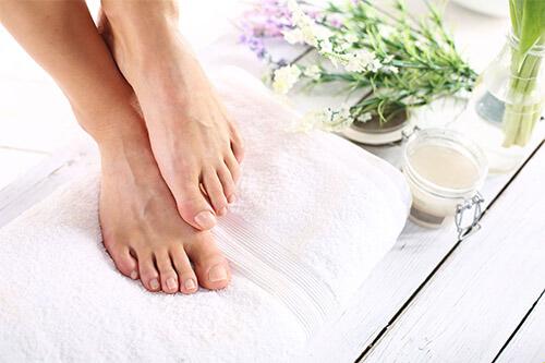 Fußpflege mit Handtuch, Creme, Öl und Blumen