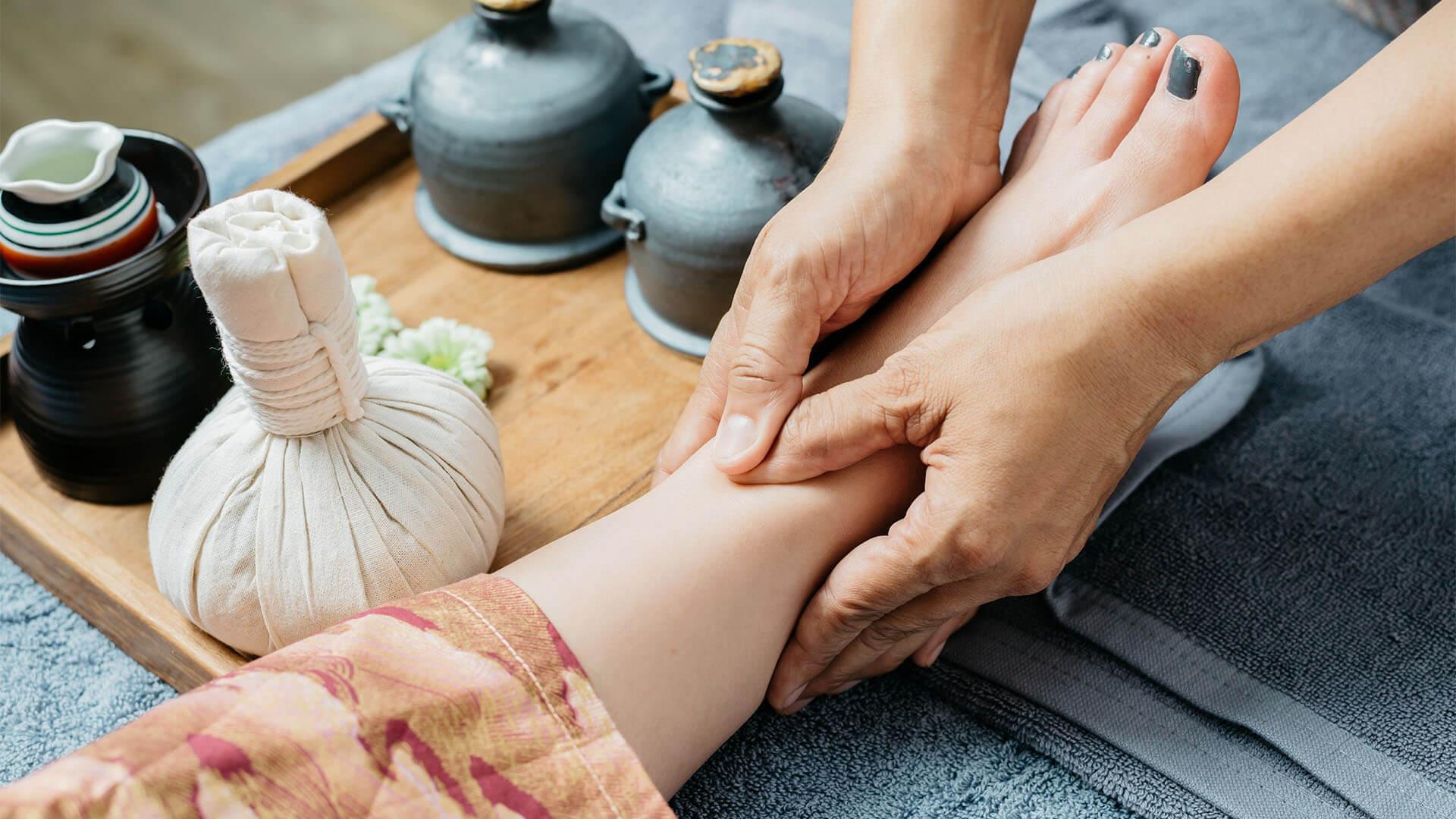 Fußreflexzonenmassage, bei der die Hände des Masseurs und ein Bein der zu massierenden Person sichtbar sind