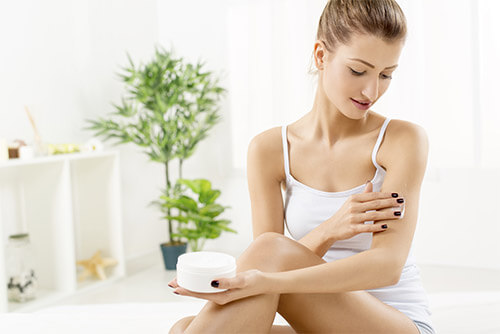 Frau trägt in hellem Zimmer eine Creme auf im Rahmen einer Körperpflege Routine