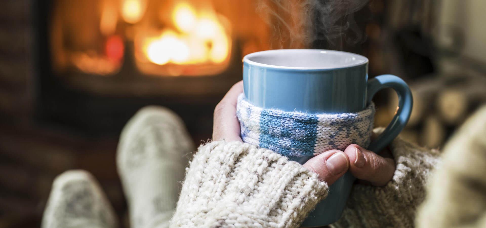 Frau vor Kamin mit warmen Tee und dicken Socken, um kalte Hände und Füße zu wärmen
