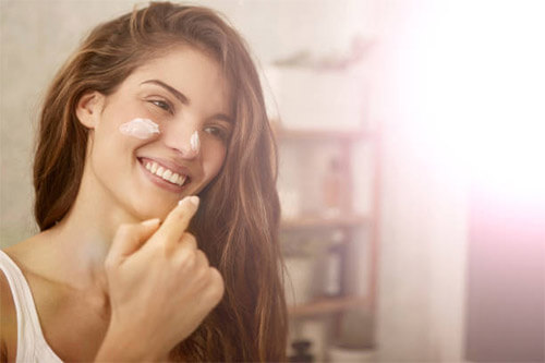 Junge Frau cremt ihr Gesicht ein, um unterirdischen Pickeln vorzubeugen