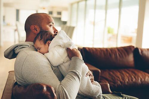 Baby schläft auf Schulter seines Vaters ein