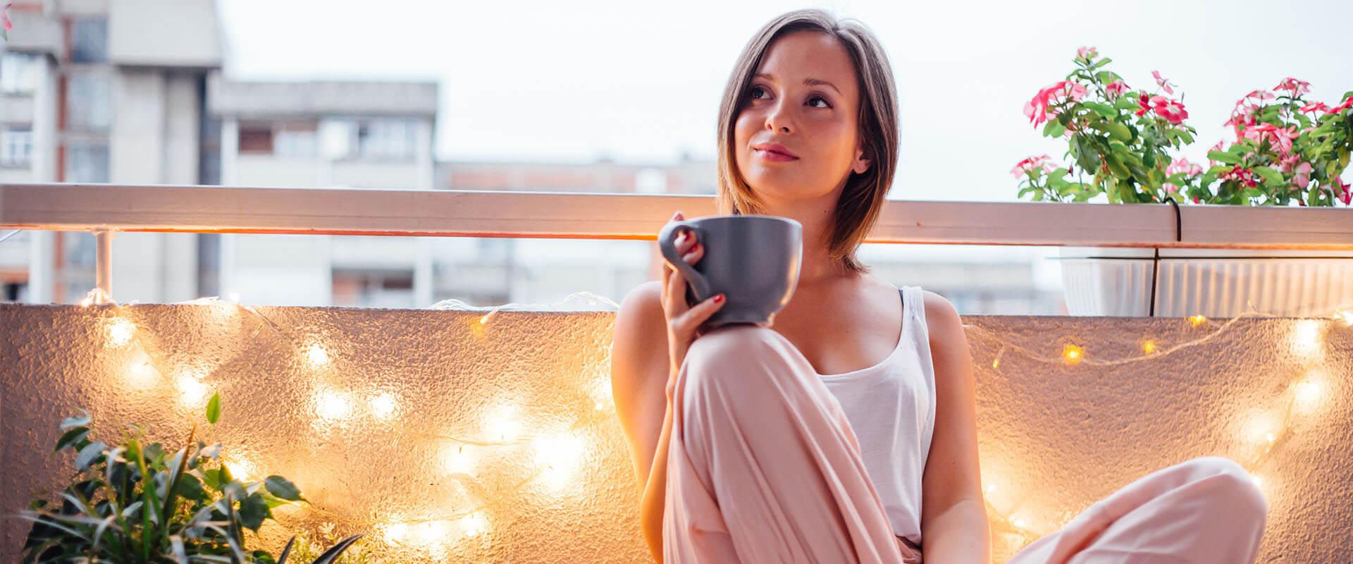 Glückliche Frau auf ihrem Balkon sitzt auf Kissen und trinkt einen Tee