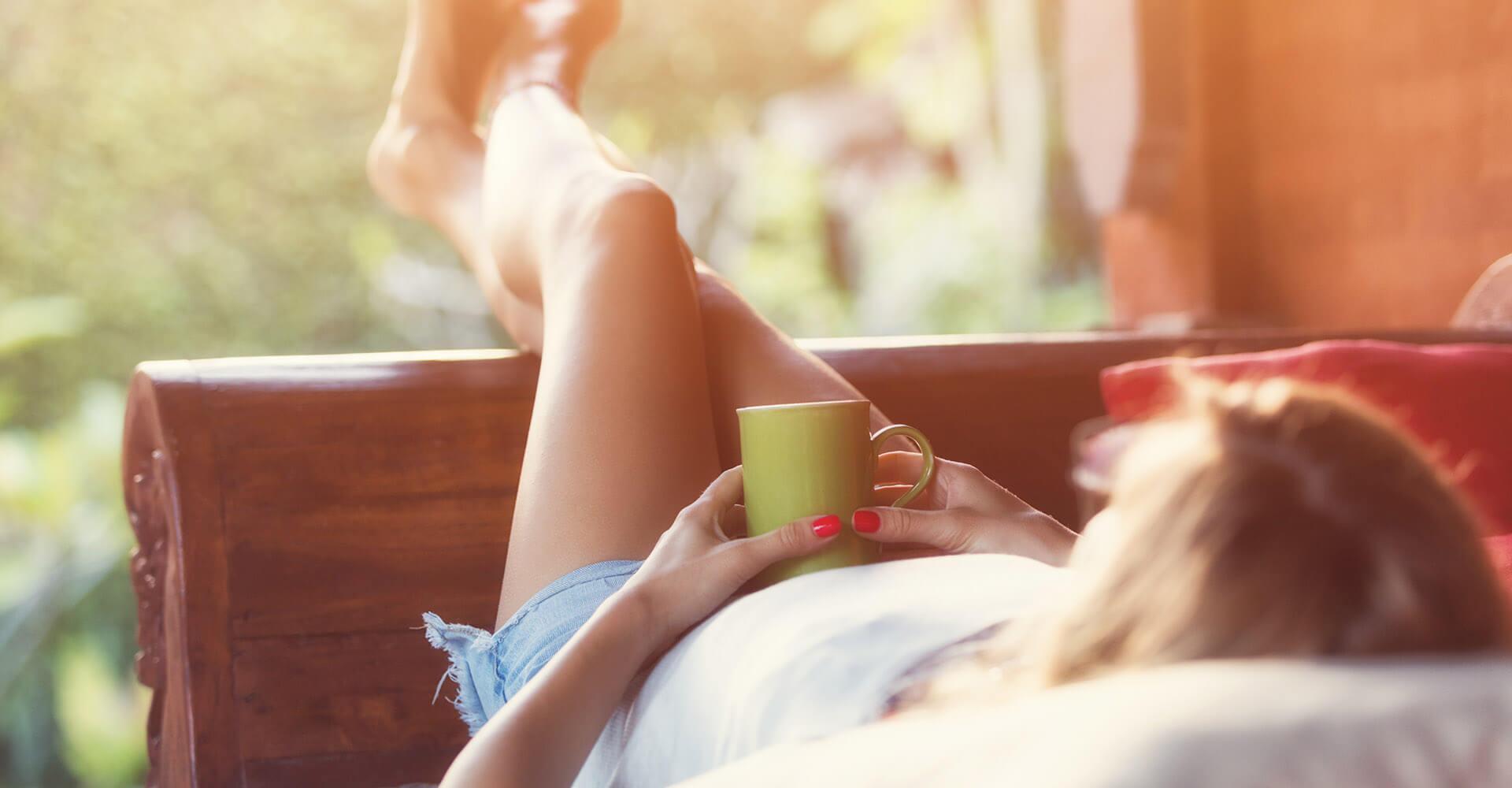 Frau liegt entspannt auf Sofa und schaut in Garten