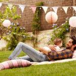 Vater liegt mit Baby auf dem Bauch im Garten auf einer gemütlichen Decke