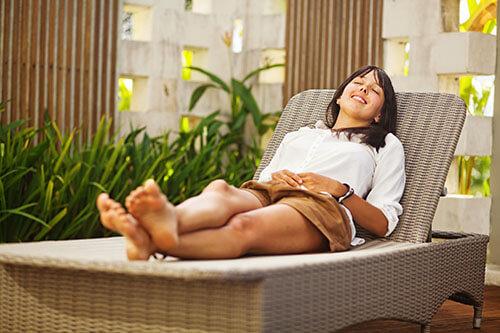 Frau entspannt auf Sonnenliege im Garten wie im Urlaub