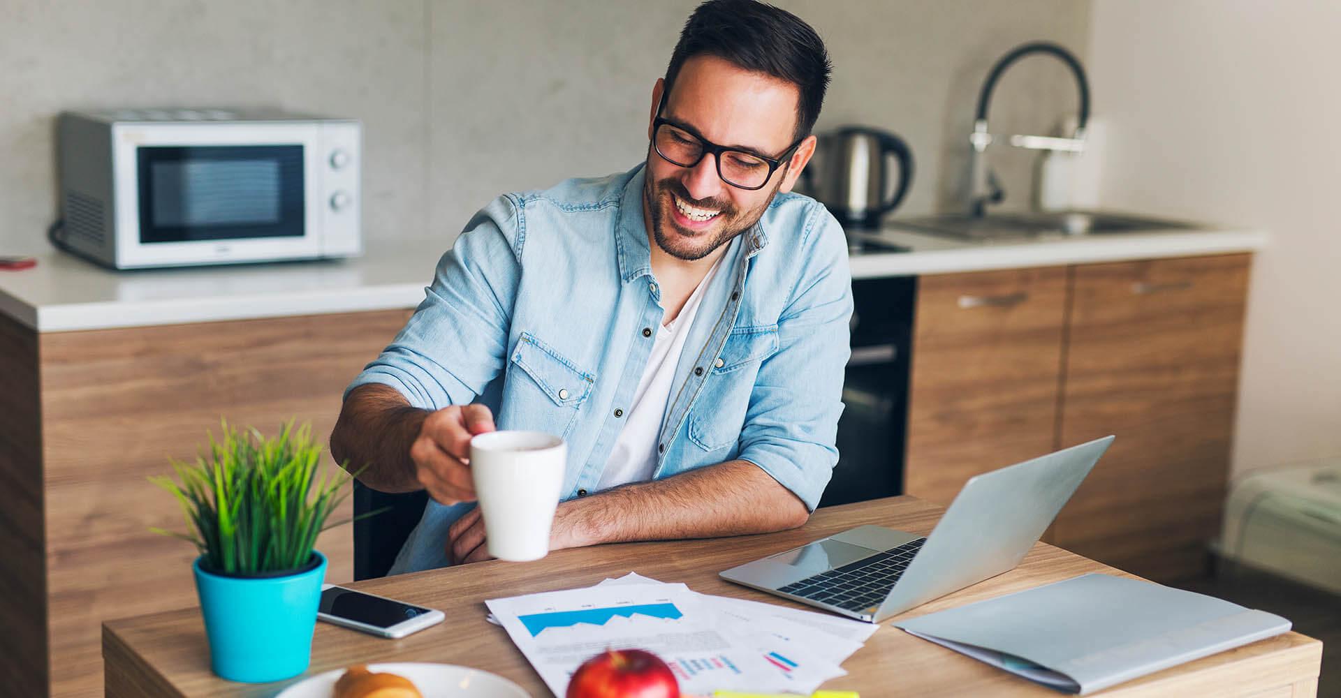 Mann sitzt am Tisch mit Kaffee in der Hand und arbeitet per Home Office