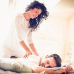 Frau gibt ihrem Partner auf gemeinsamen Bett eine Massage