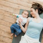 Mutter liegt mit Baby auf dem Fußboden und beide trainieren mit Hanteln