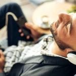 Mann entspannt auf Sofa mit Kopfhörern am Handy zu Wellness Musik