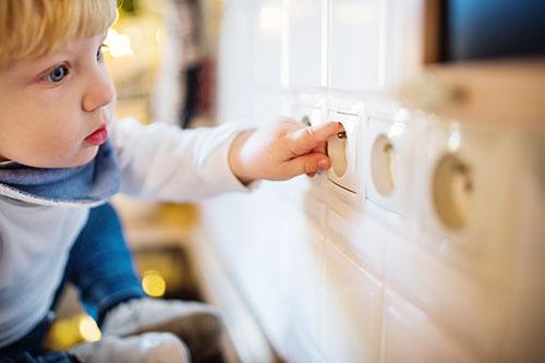 Kind steckt Finger in Steckdose - gefährliche Situation