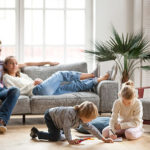 Familie im Wohnzimmer - die Eltern sitzen entspannt auf der Couch, während die Kinder ausgelassen spielen