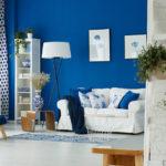 Blau und weiß gehaltenes Wohnzimmer mit Sessel, Couch, Regal und blauer Wand