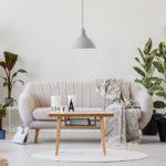 Cremefarbenes Wohnzimmer mit vielen Pflanzen und Holzelementen