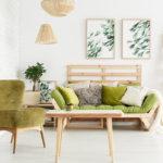 Wohnzimmer mit grünem Sessel und grünem Sofa, mit vielen Holzelementen und Pflanzen