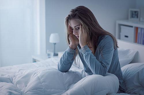 Frau wacht unausgeschlafen und unentspannt in Bett auf und hat offenbar Kopfschmerzen