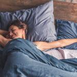 Junge Frau streckt sich glücklich im Bett nach Aufwachen