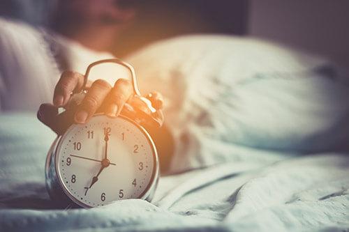 Frau mit Einschlafproblemen stellt den Wecker morgens ab