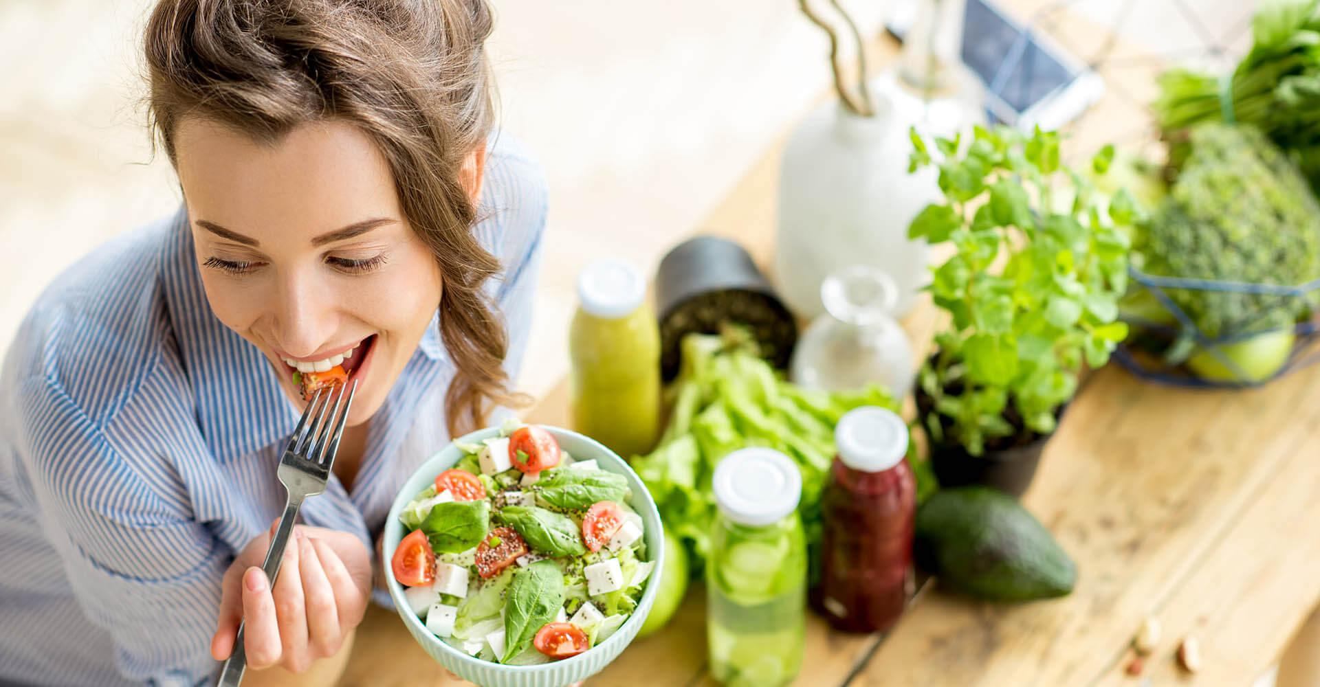 Frau isst eine Schüssel Salat, den sie sich offenbar selbst zubereitet hat