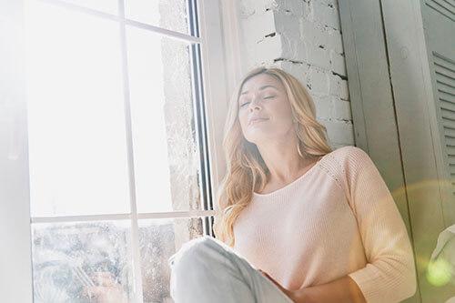 Frau sitzt am Fenster und atmet frische Luft