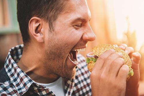 Mann ist kurz davor, in einen großen Burger zu beißen