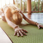 Frau macht Jogaübung auf grüner Matte zuhause