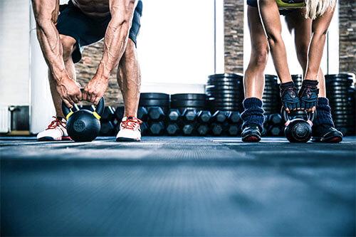 Mann und Frau betreiben zuhause Kraftsport mit Gewichten