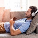 Mann schläft auf Sofa ein, während er Musik hört mit Kopfhörern