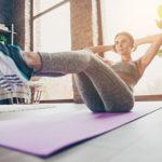 Frau macht Sit-ups im Wohnzimmer auf Isomatte und hört dabei Sportmusik