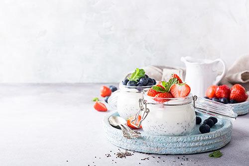 Verschiedene Superfood-Sorten wie Beeren, Erdbeeren und Chia-Samen zusammen mit Quark