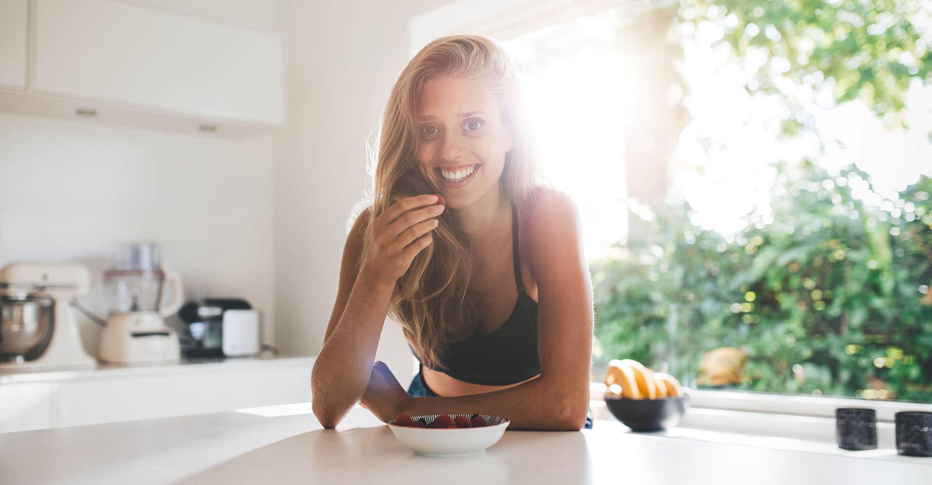 Junge Frau steht lächelnd in der Küche und isst Früchte