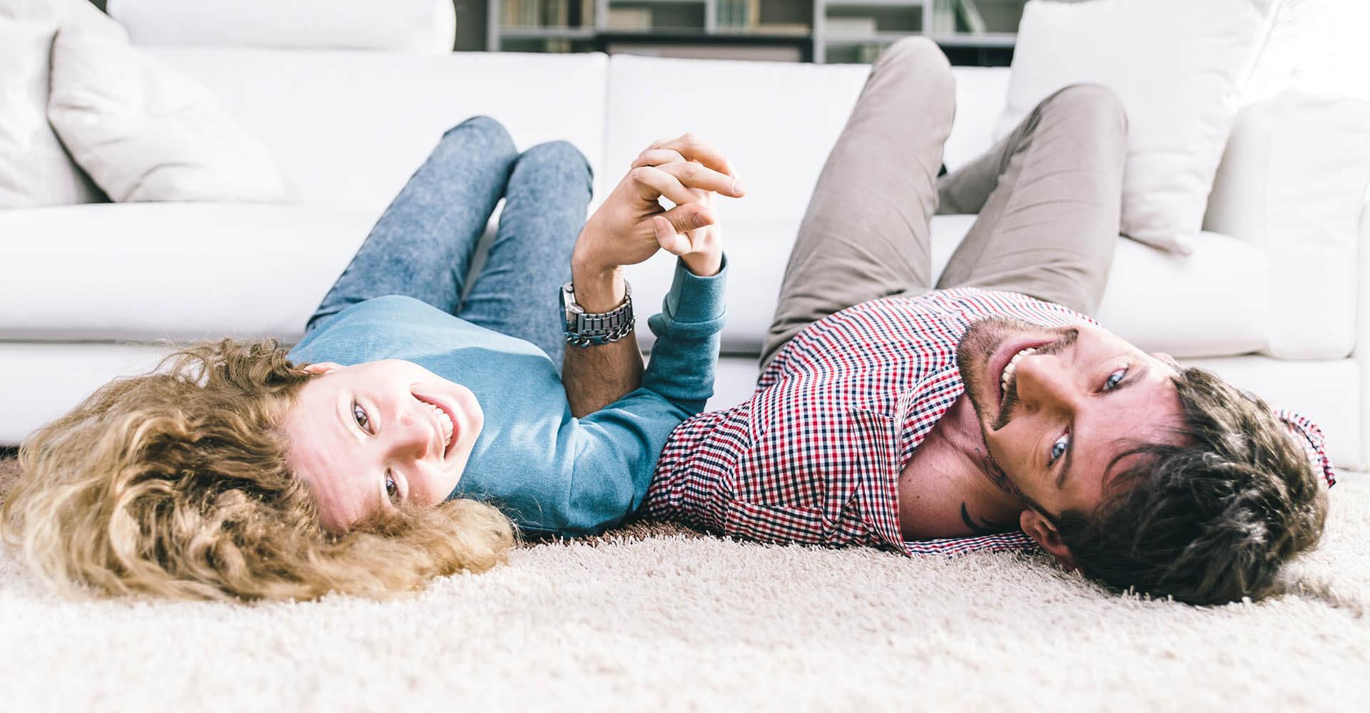 Paar wärmt sich zusammen in Wohnzimmer auf dem Boden für Yoga-Übungen auf