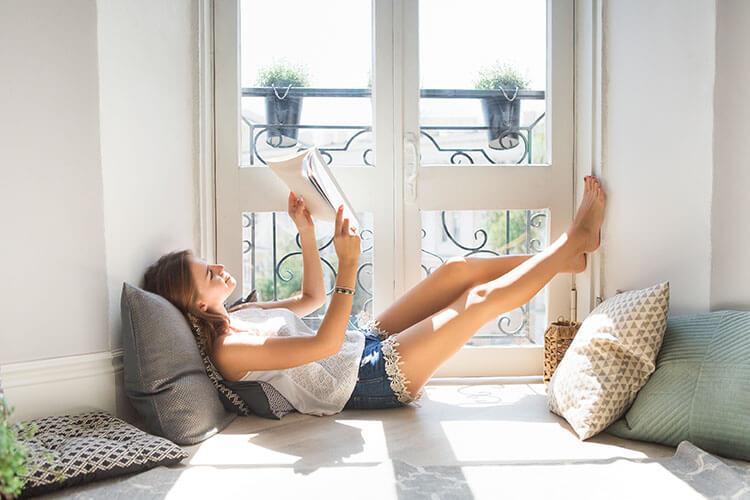 Junge Frau liest entspannt am Fenster ein Buch