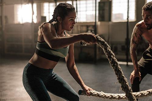 Frau führt die Crossfit-Übung Seilschwingen aus