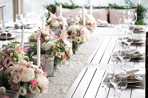 Kreative DiY-Deko auf Holztisch mit Blumen, Kerzen und Besteck