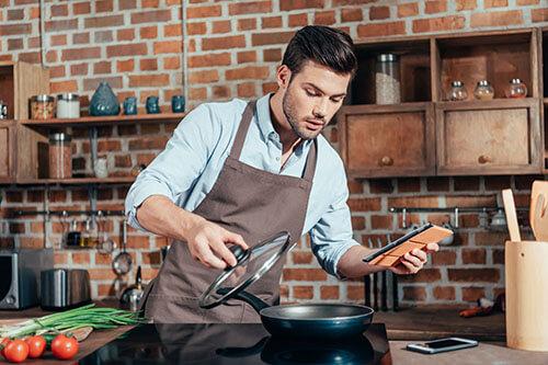 Junger Mann berechnet Eiweißwerte, während er kocht