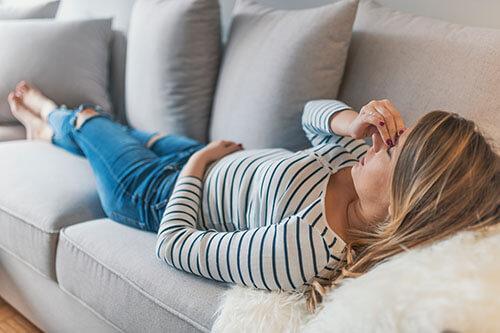 Frau liegt nach epileptischem Anfall auf dem Sofa