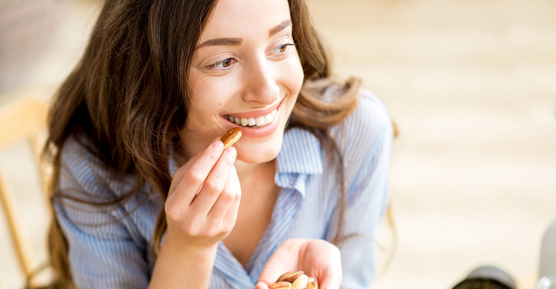 Frau isst Paranüsse im Rahmen einer ketogenen Diät