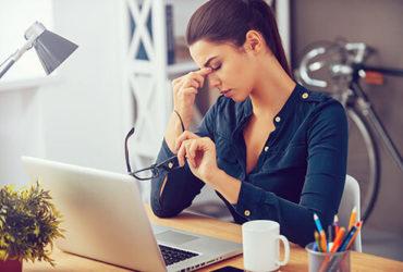 Frau hat während der Arbeit eine Migräne-Attacke