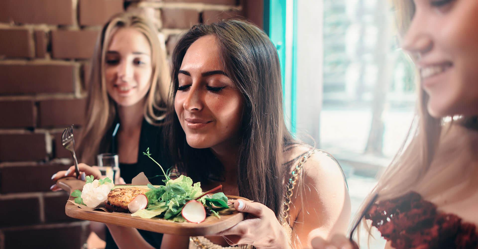 Frau riecht an ihrem gesunden Essen
